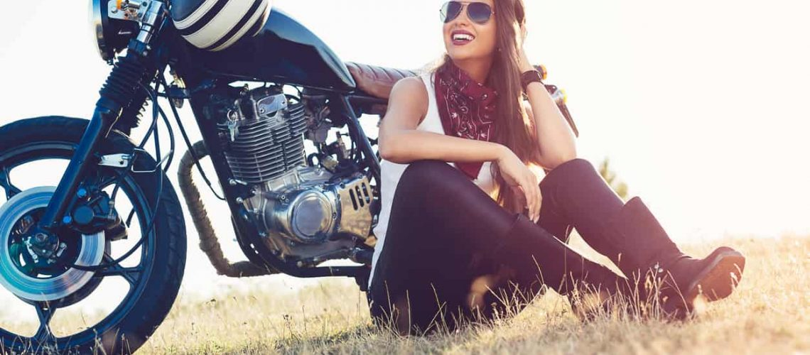 Beautiful biker woman sitting by her motorcycle on a highway
