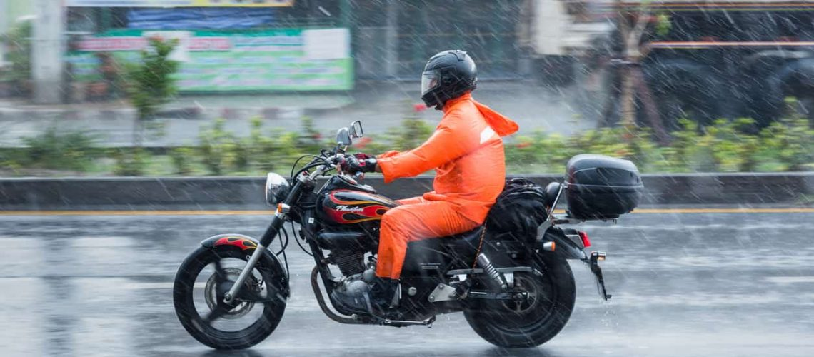 Nonthaburi: Motion Blurred panning photo of Unidentified name people riding motorcycle in the rain on road at Nonthaburi, Thailand.